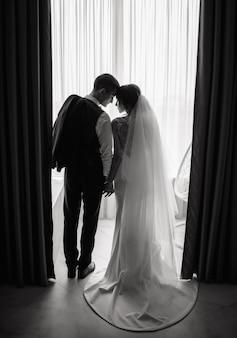 La novia y el novio están tomados de la mano frente a la ventana con las cabezas inclinadas en el hotel. boda, amor, concepto de relación. clave baja. retrato de cuerpo entero.
