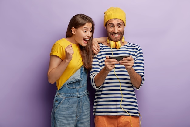 La novia y el novio felices disfrutan del nuevo juego, están satisfechos con las nuevas funciones del teléfono inteligente, miran la pantalla del dispositivo, se visten con ropa de moda, animan para ganar un maratón en línea, son adictos