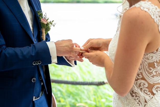 La novia y el novio intercambian anillos de boda durante el día
