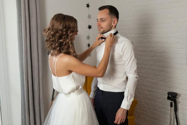 La novia y el novio por la mañana en el hotel en un día de boda.