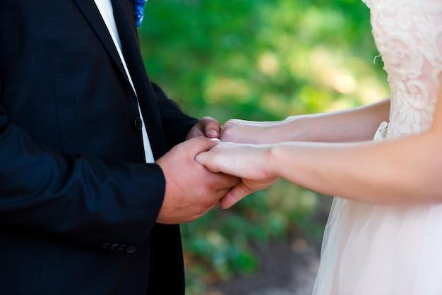 Novia y el novio de la mano en el día de la boda.
