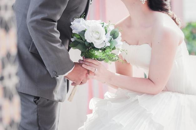 Novia y el novio de la mano y un ramo de flores hermosas