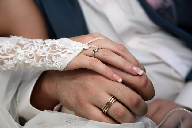 La novia y el novio muestran sus manos con anillos de boda