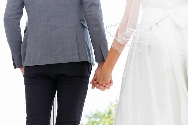 La novia y el novio pareja de caucásicos sonríen y de pie juntos de la mano.
