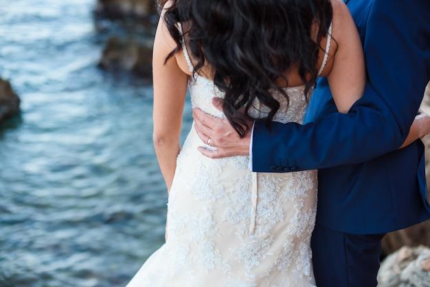 Novia y novio en la playa con un momento romántico.