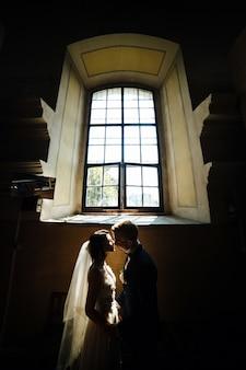 La novia y el novio posando en el fondo de una ventana grande