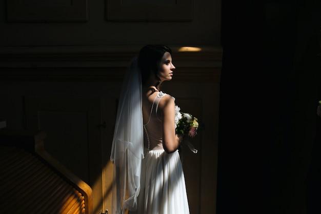 La novia y el novio posando en la habitación con poca luz
