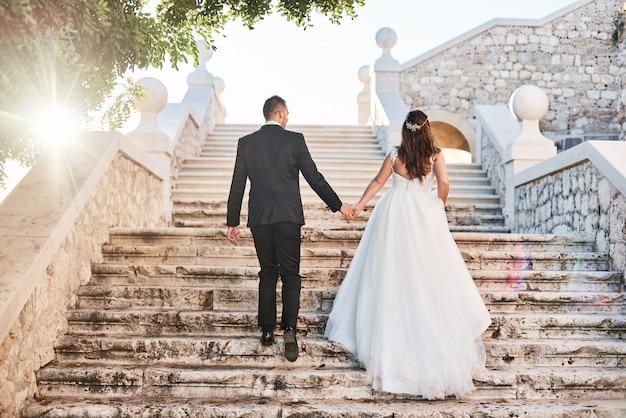 Novia y novio que caminan en castillo viejo al aire libre y que se sostienen la mano de cada uno.
