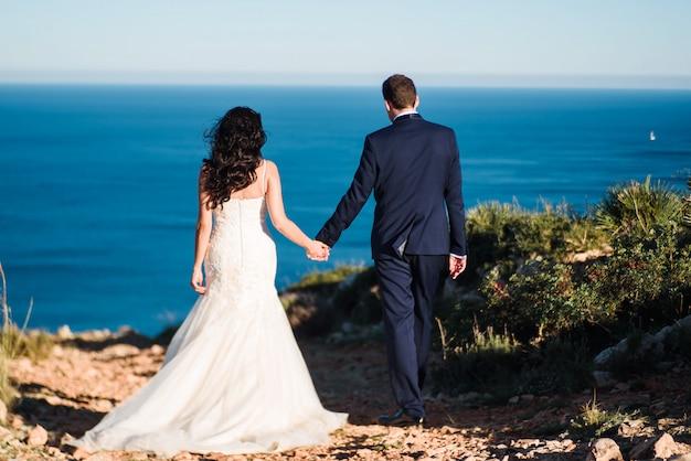 Novia y novio que caminan en la playa y que se llevan a cabo la mano.
