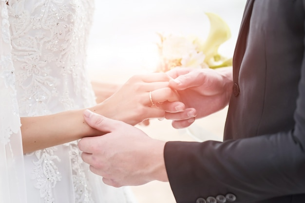 Novia y novio que llevan a cabo las manos con los anillos de bodas en el fondo del mar y del sol.