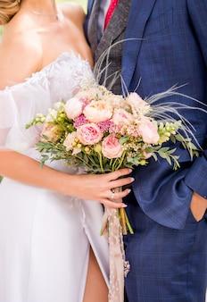 Novia y novio que sostienen el ramo hermoso de la boda de flores