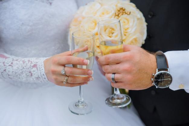 Novia y novio que sostienen los vidrios del champán de la boda