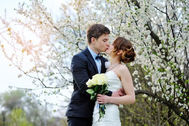 Novia y el novio con un ramo de caminar en el parque de verano