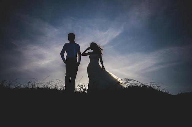 La novia y el novio retroiluminado en una puesta de sol en la playa.