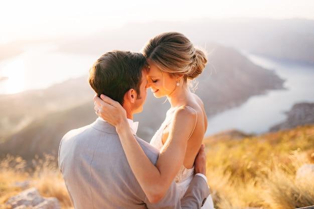 La novia y el novio sentados en la cima del monte lovcen con vistas a la bahía de kotor sonriendo y