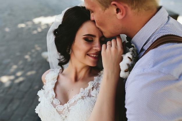 La novia y el novio se sientan en el banco y se divierten