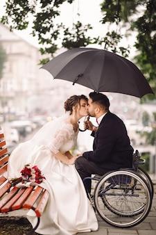 Novia y el novio en la silla de ruedas se sientan besándose en el banco en el parque