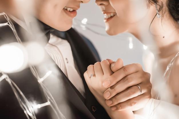 Novia y el novio sosteniendo la mano en la luz de hadas