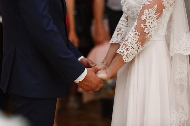 La novia y el novio sostienen suavemente las manos de cerca. día de la boda.