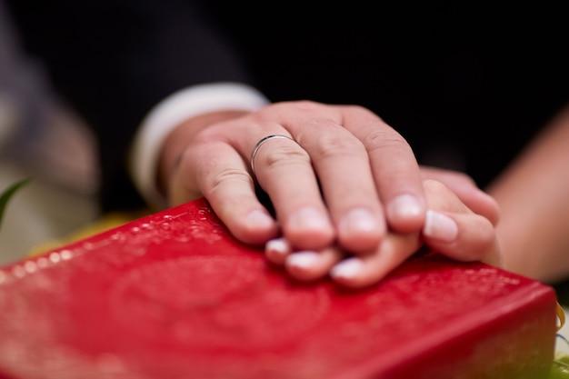 La novia y el novio sostienen sus manos sobre la biblia durante la ceremonia de compromiso en la iglesia