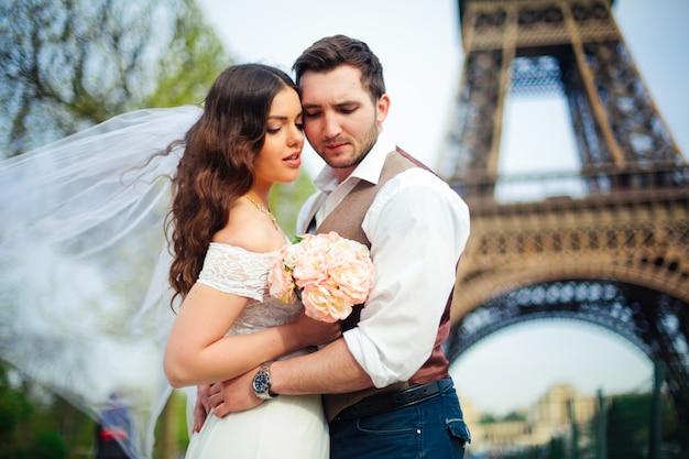 Novia y novio teniendo un momento romántico el día de su boda en parís, frente a la gira eiffel