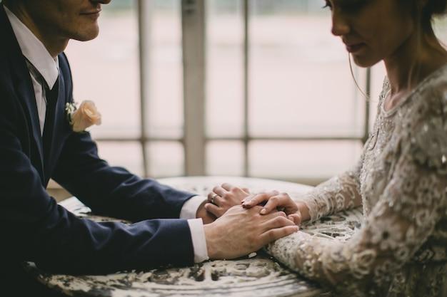 Novia y el novio tomados de la mano sobre la mesa