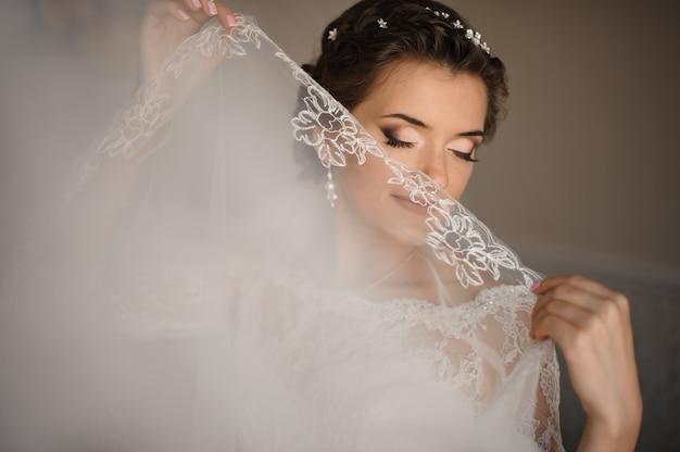 La novia con ojos azules y maquillaje suave cubre sus labios con un velo