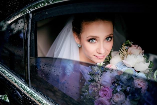 La novia con los ojos azules sostiene el ramo tierno de la boda que se sienta en el coche