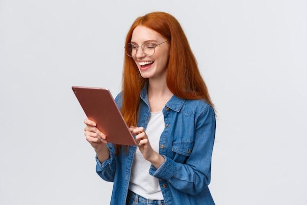 Novia pelirroja alegre hablando con pareja utilizando el servicio de videollamada de internet