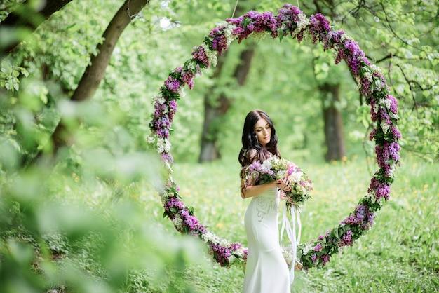 La novia con el pelo largo y oscuro se encuentra ante un gran círculo de lilas