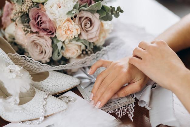 La novia pone sus manos sobre la mesa cerca de un ramo de flores, zapatos y otros detalles de novia.