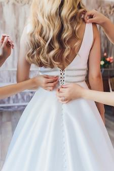 Novia poniéndose su vestido de novia blanco. concepto de celebración de boda. hermoso vestido de novia de encaje de la novia con espalda abierta.
