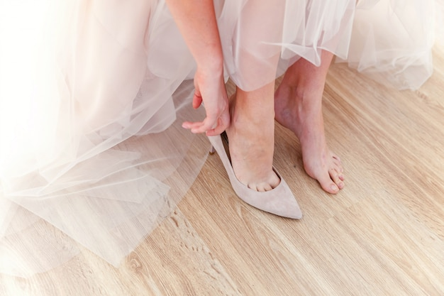 La novia se prepara para la ceremonia con hermosos zapatos a pie en el día de la boda