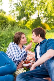 Novia que da el novio de la fresa durante comida campestre en bosque
