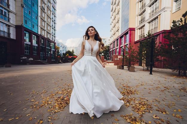 Novia que presenta en una muchacha verde del parque en un vestido blanco en un fondo del verde.
