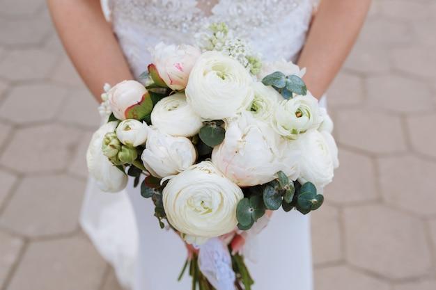 Novia con ramo de ranunculus blanco y rosa