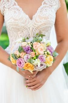 Novia con ramo, vista de cerca. ramo de novia, vestido blanco