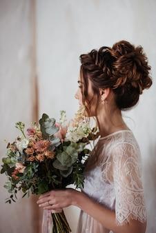 La novia se reúne por la mañana en una bata transparente. muy hermoso ramo de novia en rosa. peinado con estilo, trenzas trenzadas.