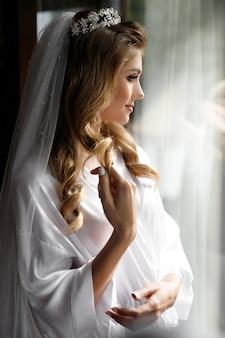 Novia rubia en la corona se encuentra ante ventana brillante en la mañana