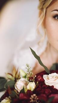 La novia rubia hermosa mira sobre el ramo rojo oscuro de la boda