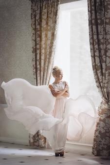 La novia rubia de la muchacha se coloca cerca de la ventana en un vestido brillante que vuela.