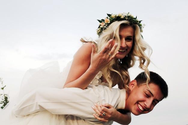 Novia rubia subida a caballito sobre su marido