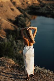 Novia sensual en un vestido de novia sexy en la orilla del lago con el viento en el pelo. vista trasera.