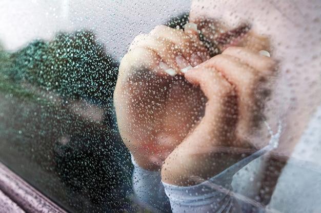 La novia sonriente cruzó las manos en forma de corazón, la vista a través del vidrio de la ventana del automóvil durante la lluvia