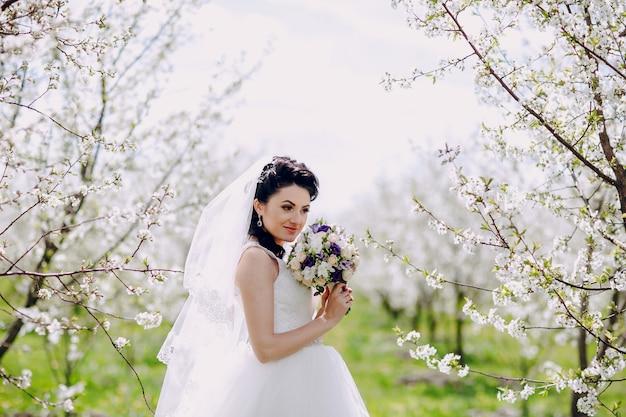 Novia sonriente posando con árboles en flor