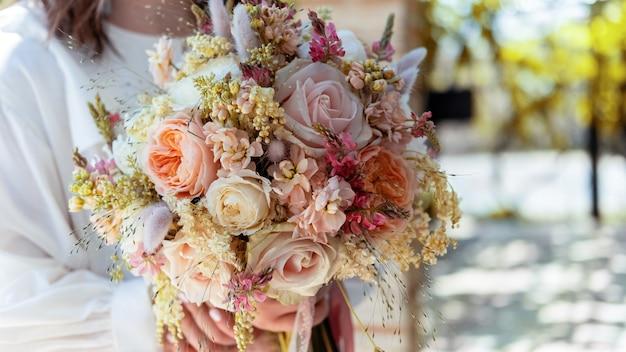Una novia sosteniendo un exuberante ramo, vista cercana, ceremonia de boda