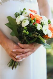 La novia está sosteniendo un hermoso ramo de novia blanco. de cerca.