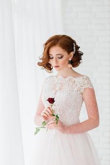Novia sosteniendo una rosa roja en sus manos