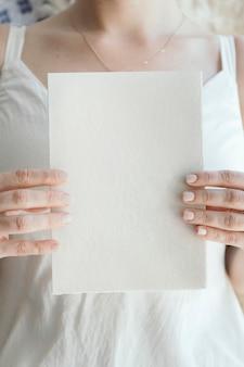 Novia sosteniendo una tarjeta blanca en blanco
