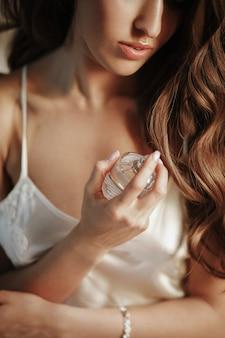 La novia sostiene una botella de perfume en sus brazos tiernos